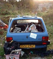 Abandoned damaged car full of rubbish