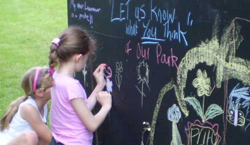 Two girls drawing on a chalkboard