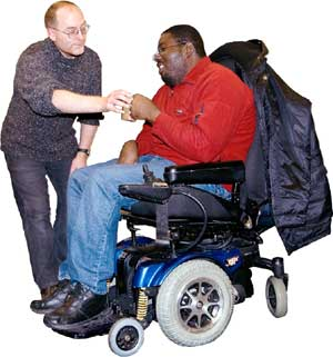 Man in a wheelchair being given a drink