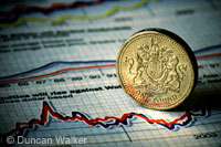 One pound coin and financial papers copyright D Walker
