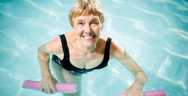 Lady smiling whilst using resistance aids in aquafit