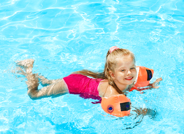 Child swimming in armbands